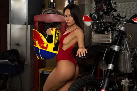 Sexy biker girl posing with helmet and motorcycle in garage