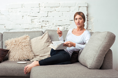 Young beautiful woman sitting on the sofa reading a book holding her tea cup in living room at home
