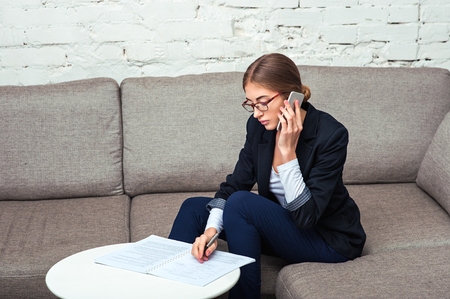 Beautiful young business woman sitting on sofa at office with documents and coffee