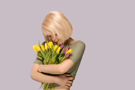 Beautiful excited smiling woman holding a bouquet of tulips on gray background 版權商用圖片