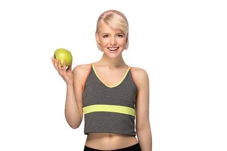 Happy smiling slim woman holding apple, studio portrait isolated on white background, healthy lifestyle concept