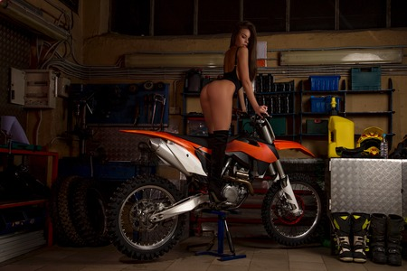 Sensual young girl in black lingerie sitting on sport motorbike in garage in sexy pose on workshop background
