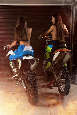 Sensual young girls in lingerie, pants and boots sitting on sport motorbikes in garage ready to ride 版權商用圖片