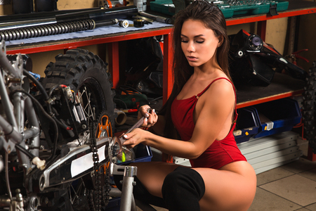Sexy model girl in red lingerie repairing motorcycle using tools in garage Stock fotó