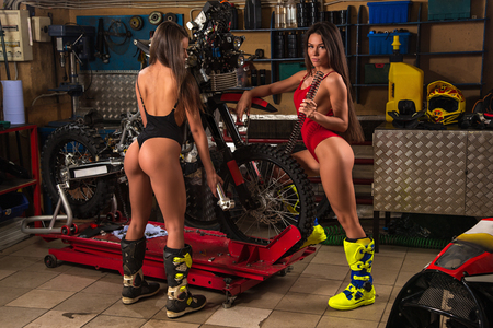 Two sexy model girls in lingerie posing with tools repairing motorcycle using tools in garage