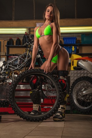 Girl in garage with motorcycle working with studded tires