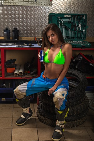 Girl in garage sitting on motorcycle studded tires and drinking lemonade