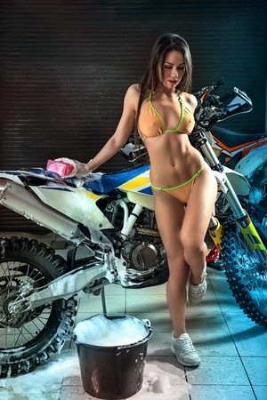 Sexy young female model girl in bikini washing motorcycle
