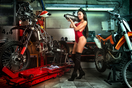 Sexy girl in garage with motorcycles posing with exhaust muffler Stock fotó