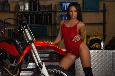 Sexy biker girl in red seductive lingerie posing with motorcycle in garage