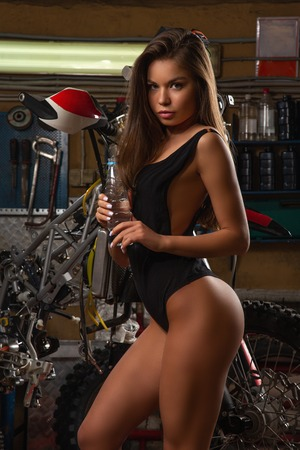 Sexy girl drinking water repairing motorcycle in garage