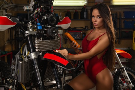 Sexy girl repairing motorcycle measuring voltage with tester in garage