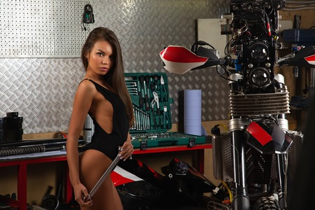 Sexy girl repairing motorcycle using tools in garage Stock fotó