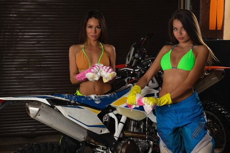 Two sexy young female models in bikini washing motorcycle