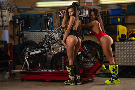Two sexy model girls in lingerie and moto boots posing with motorcycle in garage
