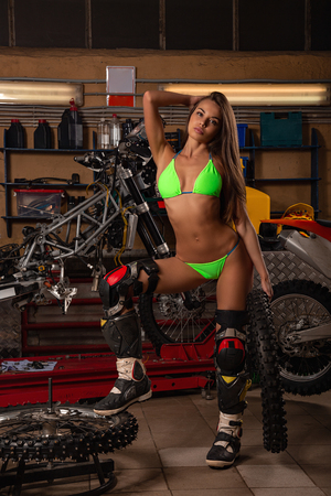 Girl in garage with motorcycle working with bike tires Stock fotó