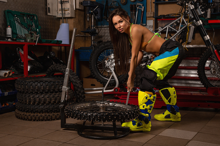 Sexy girl in garage with motorcycles changing studded tires Stock fotó