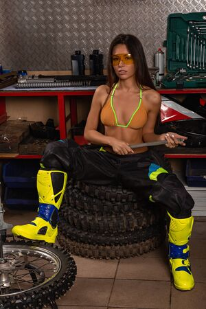 Girl in garage with motorcycle working with bike tires and wrench 版權商用圖片 - 127261194