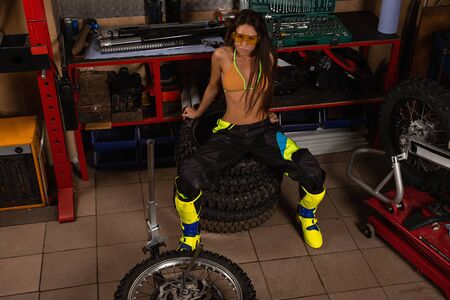 Girl in garage with motorcycle sitting on bike tires