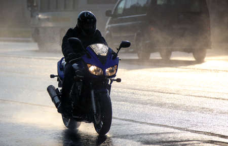 A young man on a motorcycle rides along a busy highway on a rainy day. Banque d'images