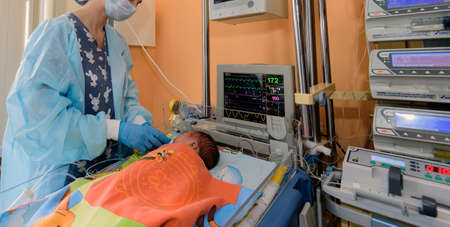 A young nurse caring for a newborn in a hospital in the intensive care unit.