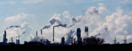 Air pollution from smoke coming out of factory chimneys. Stock Photo