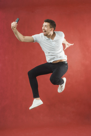 Photo of excited bearded man jumping over red background wall using mobile phone make selfie.