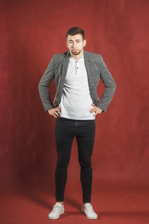 Full length portrait of bearded hipster man standing over red background and looking at the camera Banque d'images