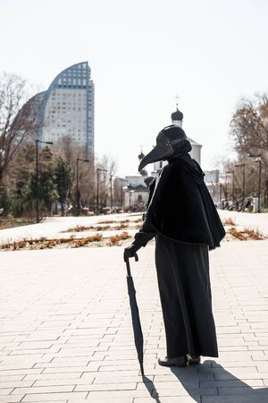 plague doctor in an empty city on the background of the temple Banco de Imagens