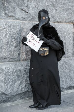 plague doctor holds a sign saying wash your hands
