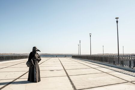 plague doctor alone on a large paved area Banco de Imagens