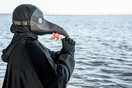 plague doctor in an empty city on an empty marina holds a flower Banco de Imagens