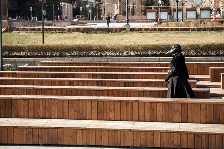 plague doctor in an empty city park Banco de Imagens