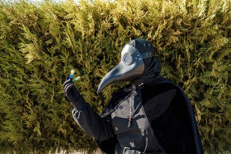 plague doctor holds a vaccine against a background of plants