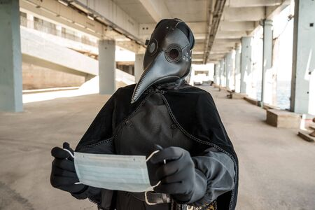 plague doctor holding a mask in an empty city on an empty marina