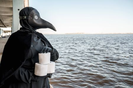 plague doctor holding toilet papers in an empty city on an empty marina Banco de Imagens