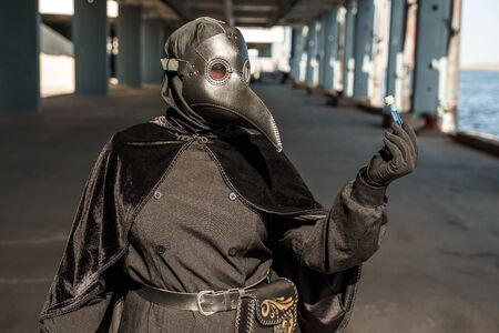 plague doctor in empty city on empty pier holds vaccine