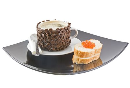 The coffee cup , original decorated by coffee grains(beans) with red caviar on black plate. photo
