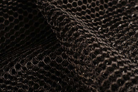Black texture. A black net is placed on a black perforated metal table. The light glares.