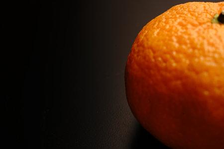 Tangerine close on black background. Dim light that highlights the fruit.