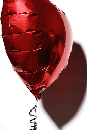 A heart inflated with helium flies on a string on a white background. A gift for Valentines Day. Stock fotó