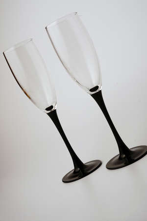Two alcohol glasses with black legs on a white background. Slightly tilted.