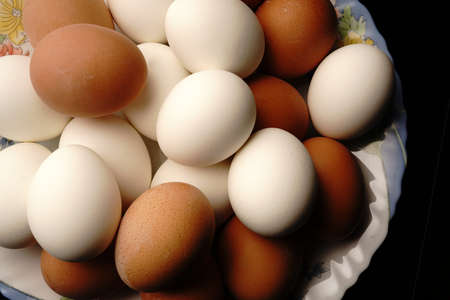 A lot of white and brown chicken eggs are on the plate. Top view.
