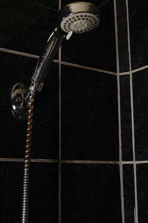 The shower handle is chrome-plated. On the background is a black shower tile.