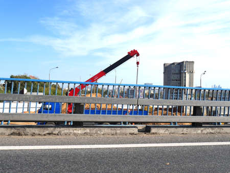 Construction work on laying a new road and pipes with a crane. Summer. Blue sky