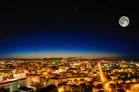 lake dwelling: beautiful city at night from the height of the full moon with a clear starry sky at sunset Stock Photo