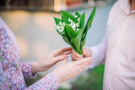 Mans and womans hands with nosegay of lily of the valley Stock Photo