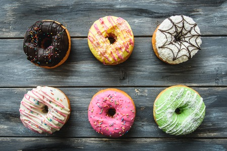 gamme de produit: Multi-colored assortment of donuts with sprinkles and frosting on light wooden background. six sweet rings