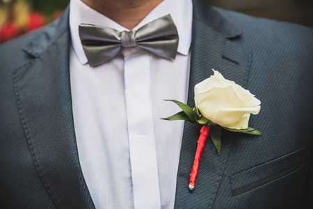 lapel: close-up portrait of stylish groom in a blue suit with a tie and a flower buttonhole butterfly on the lapel on the wedding day
