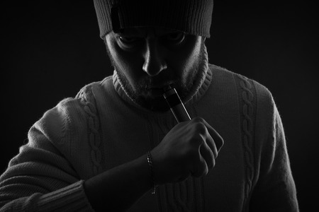 non violence: Men with beard vaping on black background in hat. Stock Photo